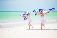 Little girls having fun running with towels on tropical beach Stock Photography