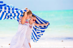 Little girls having fun running with towels on tropical beach. Kids enjoy their family summer vacation in the Indian Royalty Free Stock Photos