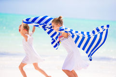 Little girls having fun running with towels on tropical beach with white sand and turquoise ocean water Royalty Free Stock Image