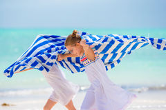 Little girls having fun running with towels on tropical beach with white sand and turquoise ocean water Stock Images
