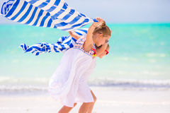 Little girls having fun with towels on tropical beach Stock Photo