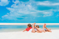 Little girls having fun at tropical beach lying together on the seashore Royalty Free Stock Photos