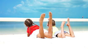 Little girls having fun at tropical beach lying together on the seashore. SLOW MOTION. Cute little girl at beach during summer vacation stock footage