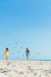 Little girls having fun at tropical beach playing together on the seashore Stock Photography