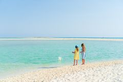 Little girls having fun at tropical beach playing together on the seashore Stock Image