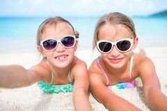 Little girls having fun at tropical beach playing together at shallow water. Adorable little sisters at beach during royalty free stock images