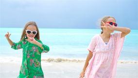 Adorable little girl having a lot of fun at tropical beach playing together background turquiose water and blue sky. Little girls having fun at tropical beach stock video