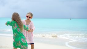 Adorable little girl having a lot of fun at tropical beach playing together. Little girls having fun at tropical beach playing together at shallow water stock footage