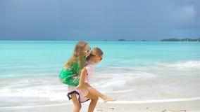 Little girls having fun at tropical beach playing together. SLOW MOTION. Little girls having fun at tropical beach playing together at shallow water stock video