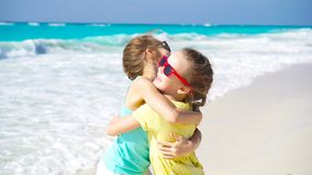 Little girls having fun at tropical beach playing together. Adorable little sisters at beach during summer vacation. Little girls having fun at tropical beach stock video footage