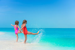 Little girls having fun at tropical beach playing together at shallow water Royalty Free Stock Photos