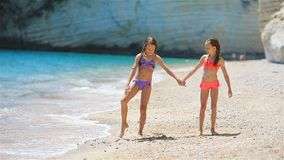 Little girls having fun at tropical beach during summer vacation