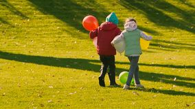 Little girls holding balloons are kicking another green balloon. Two little girls holding balloons are running and kicking another green balloon. Slow motion stock footage