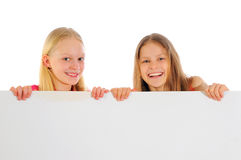 Little girls holding blank sign. Two little girls holding a blank sign isolated on a white background Royalty Free Stock Photo