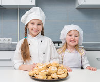 Little girls holding a bowl with homemade cookies. Cute little girls holding a bowl with homemade cookies stock photography