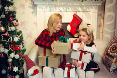 Little girls holding presents by the Christmas tree Stock Images