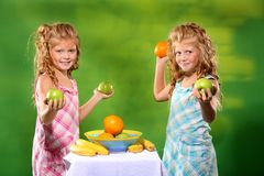 Little girls holding some fruit. Little twin sisters holding apples and oranges on the green background Stock Photo
