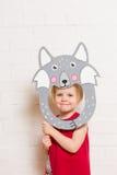 Little girls holding wolf mask on white background Stock Photo