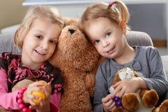 Little girls huddling up against teddy bear stock photography