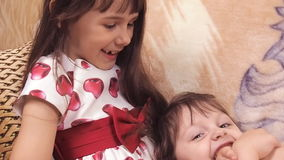 Little girls hug. Sisters hug each other. The children are playing on the couch. Girls in dresses. stock video