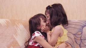 Little girls hug. Sisters hug each other. The children are playing on the couch. Girls in dresses stock footage
