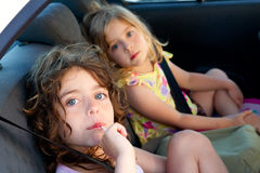 Little girls inside car eating candy stick. Selective focus Stock Image
