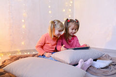 Little girls involved in use of tablet and sit on floor in brigh. Cute little girls play in computer games on device or watch cartoons, press something on touch Royalty Free Stock Image