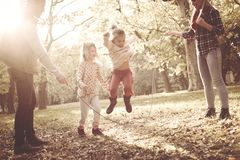 Little girls jumping across jump rope parents holding rope royalty free stock photos