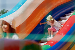 Little girls in a jumping castle. Young girls playing in a bouncing castle in a bright sunny day Stock Images