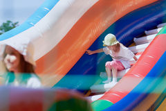 Little girls in a jumping castle. Young girls playing in a bouncing castle in a bright sunny day Stock Photos