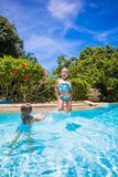 Little girls jumping and having fun in swimming Royalty Free Stock Image
