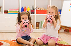 Little girls kissing the piggybanks. Two little girls kissing the piggybanks and sitting on the floor Royalty Free Stock Photography