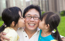Little girls kissing their father. Happy little girls kissing their father Royalty Free Stock Photography