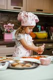 Child kitchen girls cook apron cupcake cookies small funny three sisters cap cream cream decor royalty free stock images