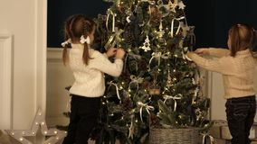 Little girls knitted sweaters hanging ornaments on Christmas tree in lights. stock images