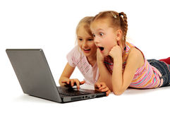 Little girls with laptop. Two little girls with a laptop computer isolated on a white royalty free stock images