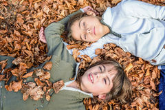 Little girls laying on the bed of leaves in national park Biogra Royalty Free Stock Photos