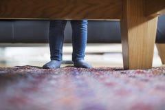 Little girls legs at home. Little girls legs at home standing behind sofa Stock Image