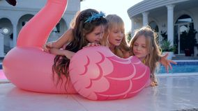 Little girls lie on inflatable pink flamingo near pool, kids celebrities in swimsuit on summer vacation, spoiled rich stock video