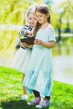 Little girls listening to music on headphones in a spring park outdoor Stock Photography