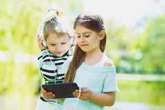 Little girls listening to music on headphones in a spring park outdoor Stock Photos
