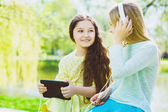Little girls listening to music on headphones in a spring park outdoor Stock Images
