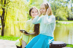 Little girls listening to music on headphones in a spring park outdoor Royalty Free Stock Photo