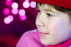 Little girls look with Christmas lights Stock Images