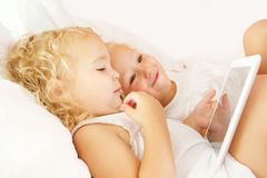 Little girls looking at digital tablet on bed. Side portrait of little girls looking at digital tablet on bed stock photos