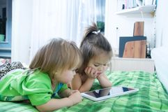 Little girls looking on pad lying on bed at home. Children time spending stock photos