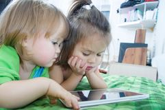 Little girls looking on pad lying on bed at home stock images
