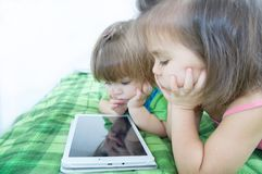 Little girls looking on pad lying on bed at home. Children time spending. Kids using tablet royalty free stock image