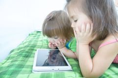 Little girls looking on pad lying on bed at home. Children time spending. Kids using tablet stock photos