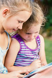 Little girls looking at tablet outdoors. Stock Photo